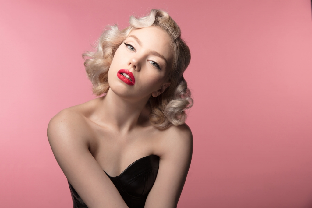Blonde model with bright red lips posing in front of a pink backdrop